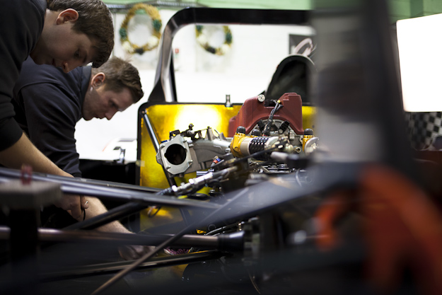 Behind the scenes shot showing the car opened up being worked on by the engineers.