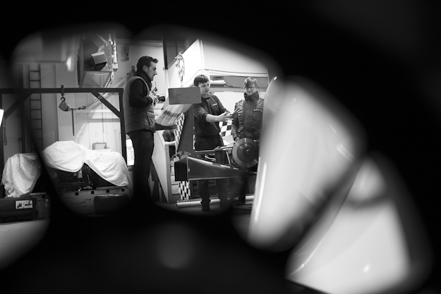 Behind the scenes, black and white, shot looking through a wheel rim to show the rear of the car along with Cal Carey Photographer and engineers.