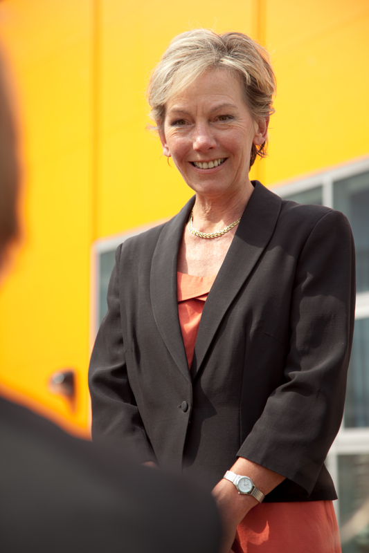 Professional commercial photography shot showing a portrait shot of a woman with the yellow of the building out of focus in the background. Shot by professional northeast commercial photographer Cal Carey.