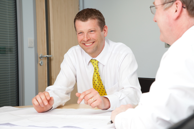 Professional commercial photography shot showing a man sat at a table, grinning with another man on the right of the frame in the foreground and out of focus. Shot by professional northeast commercial photographer Cal Carey.