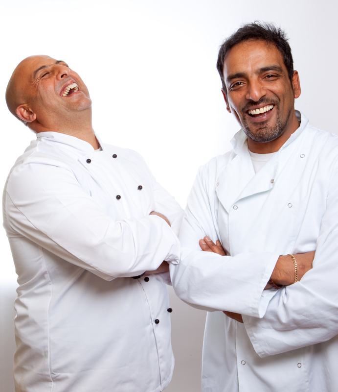 Professional commercial shot showing a mid-shot of two chefs, one of them with their head back laughing and the other smiling straight into camera. Shot by professional northeast commercial photographer Cal Carey.