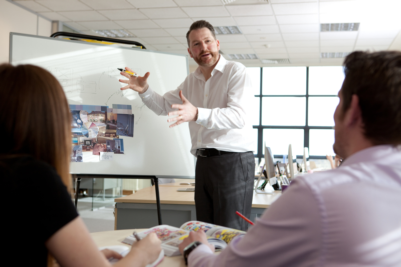 This is a professional photograph of the Velvet Communications brand manager enthusiastically presenting a project, with a whiteboard in the background and his two co-workers giving feedback and reacting to his project. Shot by professional northeast commercial photographer Cal Carey.