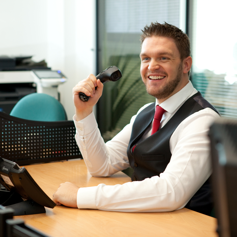 Professional commercial shot showing a man at his desk with a phone in hand, smiling. Shot by professional northeast commercial photographer Cal Carey.