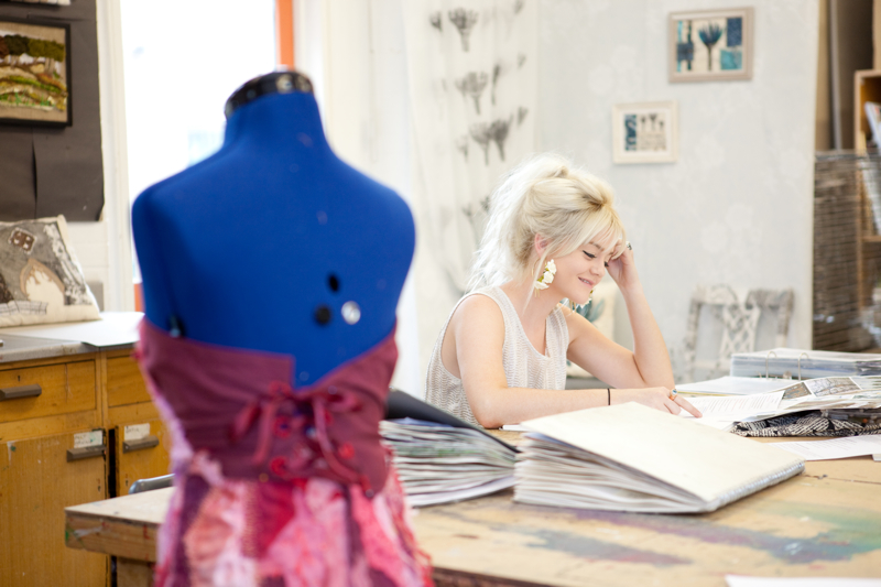 Professional advertising shot showing a young girl at a desk with a mannequin out of focus in the foreground. Shot by professional northeast advertising photographer Cal Carey.