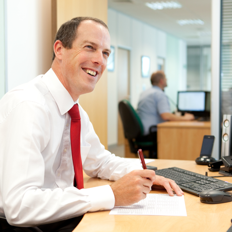 Professional commercial shot showing a mid-shot of a man sat at his desk writing but smiling looking upwards. Shot by professional northeast commercial photographer Cal Carey.