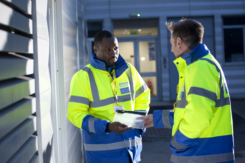 Professional commercial shot showing two Vistech security guard, both in high-visibility coats, showing an example of 'key holding'. Shot by professional northeast commercial photographer Cal Carey.