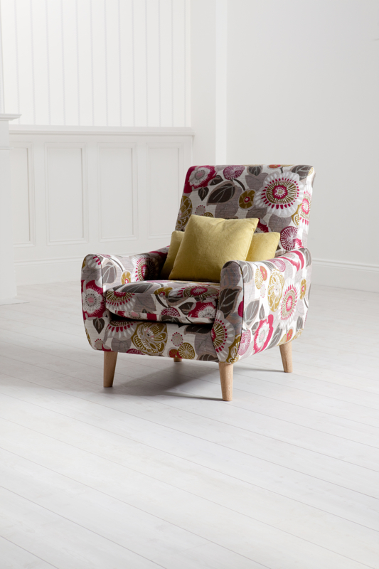 A patterned Barker & Stonehouse armchair, lamp and sofa in a light room set.