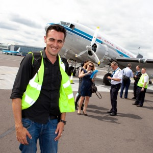 Behind the scenes shot showing Cal Carey Photographer posing for a photograph with a KLM plane behind him.