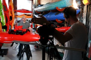 Behind the scenes shot showing Cal Carey Photography shooting video at Typhoon with colourful kayaks in the background.