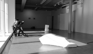Black and white behind the scenes shot showing Cal Carey Photographer shooting a piece of art.