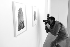 Black and white behind the scenes shot showing Cal Carey Photographer shooting art on the walls.