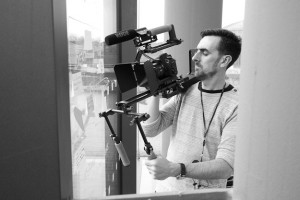 Black and white behind the scenes photography shot showing Cal Carey Photographer using the shoulder rig with the DSLR attached to film with.