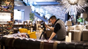 Behind the scenes shot showing Cal Carey the professional advertising photographer sat down looking at his camera, on a tripod, whilst on a professional advertising photography shoot for clients Barker & Stonehouse.