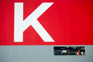 Professional industrial and transport shot which is a close up of the K-Line ship showing the letter K in white surrounded by red. Just below is a worker on the ship which just shows the vastness of the ship. Shot by professional north-east photographer Cal Carey.