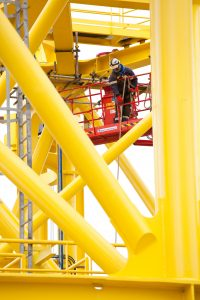 This is a professional industrial photograph of a worker helping on a vibrant yellow undersea platform structure, Shot by the professional northeast photographer Cal Carey.