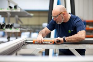 This is a professional shot by Northeast Industrial photographer Cal Carey. In this shot the PSP UK Ltd worker is applying glue to an aluminium frame.