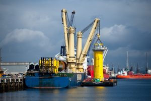 Professional industrial photography shot for PD Ports showing a ship loading a bright yellow wind farm base onto a barge in Teesport Docks Northeast UK. Shot by professional northeast industrial photographer Cal