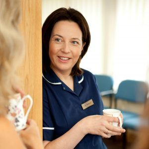 Professional commercial shot showing a nurse talking to somebody out of frame, save their hair, with a mug in hand. Shot by professional northeast commercial photographer Cal Carey.