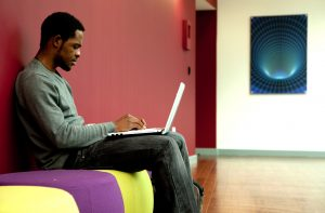 Professional advertising shot showing a young man to the left of the frame sat on colourful seats while on his laptop. Shot by professional northeast advertising photographer Cal Carey.