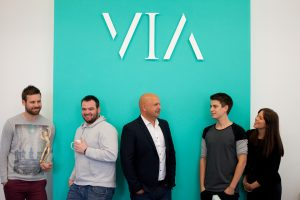 Professional commercial shot showing 5 people in a row underneath the VIA logo on a aqua background. Shot by professional northeast commercial photographer Cal Carey.
