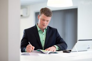This is a corporate shot of a suited Greenbank employee working in an office setting in Middlesbrough, Teeside.