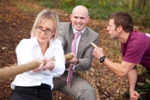 Professional advertising photography shot showing a man and a woman, in office wear, tugging rope in the woods whilst being shouted at by an instructor. Shot by professional northeast advertising photographer Cal Carey.