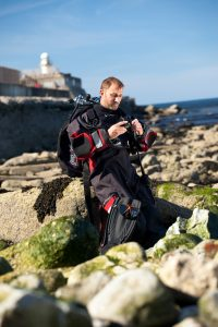 Professional advertising shot showing a man in full diving gear sat on rocks at south gare, Redcar. Shot by professional northeast advertising photographer Cal Carey.