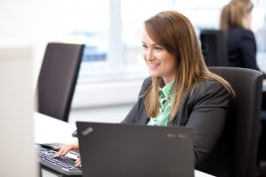 A portrait photograph of a female member of staff at Greenbank working on a computer. Shot by professional northeast commercial photographer Cal Carey.